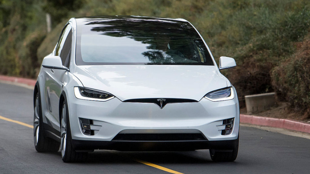 The Tesla Motors Inc. Model X sport utility vehicle (SUV) is driven during an event in Fremont, California, U.S., on Tuesday, Sept. 29, 2015. Elon Musk handed over the first six Model X SUVs to owners in California Tuesday night, as Tesla reached a milestone of having two all-electric vehicles in production at the same time. Photographer: David Paul Morris/Bloomberg via Getty Images